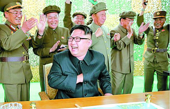 북한 김정은 노동당 위원장(가운데)이 2017년 8월 화성-10(무수단 미사일)' 시험발사에 성공한 뒤 웃고 있는 모습. 김낙겸 전략군사령관(왼쪽 첫번째) 등 수행원들이 미사일 발사에 성공한 뒤 박수를 치고 있다.   [사진제공=노동신문]