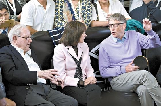 워런 버핏 버크셔 해서웨이 회장(왼쪽)과 빌 게이츠 마이크로소프트 설립자(오른쪽)가 미국 오마하에서 열린 버크셔해서웨이 주총에서 대화를 나누고 있다. 두 사람은 미국의 유산기부 운동을 주도하고 있다.