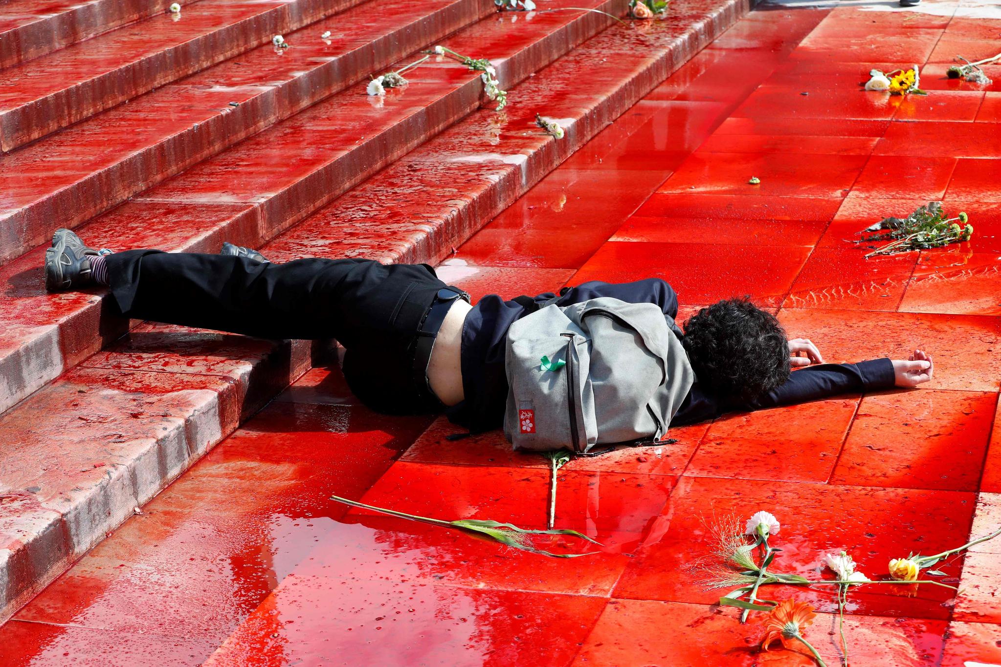 한 시위대가 가짜 피가 뿌려진 바닥에 누워 시위를 하고 있다. [AFP=연합뉴스]