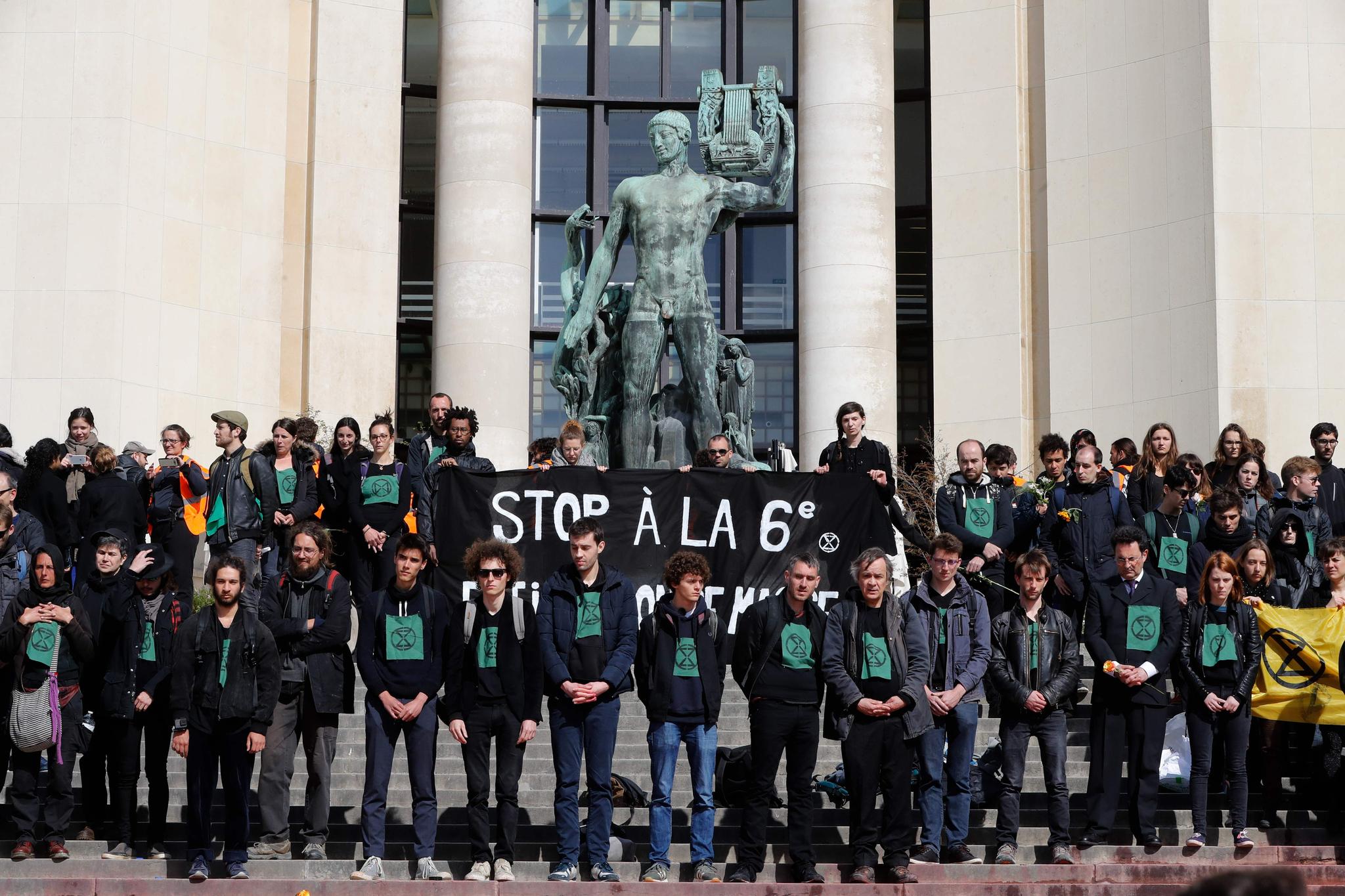 검은옷을 입은 멸종저항 시위대가 계단을 청소하기 전 몇 분간 침묵을 하는 시위를 하고 있다. [AFP=연합뉴스]