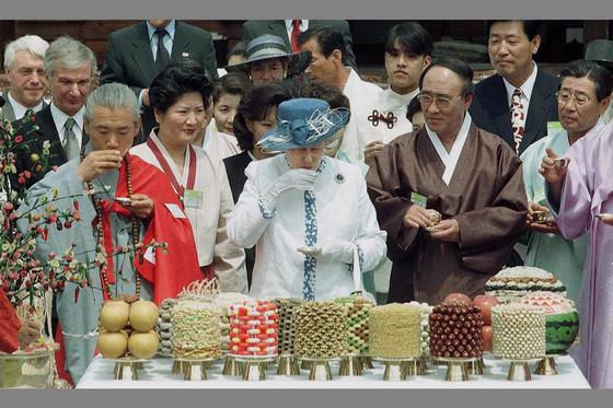 엘리자베스 영국 여왕이 1999년 4월 21일 경북 안동 하회마을을 방문, 옛 사대부의 전통가옥인 담연재에서 안동소주 기능보유자 조옥화 우리음식연구회장이 차린 73회 생일상을 받고 전통청주로 축배를 들고 있다. [중앙포토]