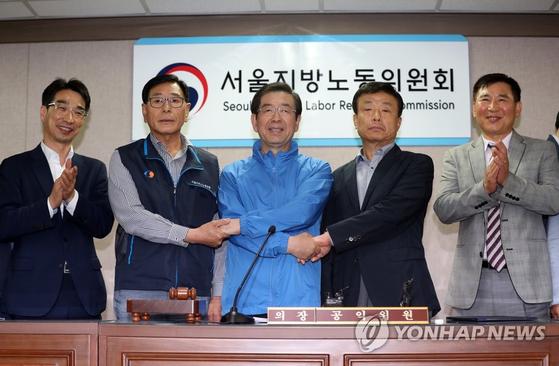 서울 시내버스 노사가 15일 파업을 불과 2시간 앞두고 임금 및 단체협약 협상을 타결했다. 박원순 시장(가운데)과 노사 관계자 등이 기념촬영을 하고 있다.[연합뉴스]