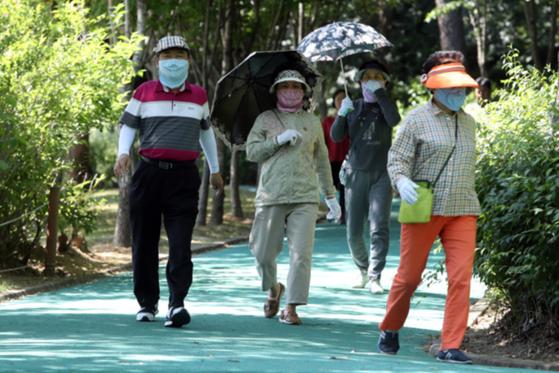 자외선 노출이 문제 되지 않은 날 아침에도 얼굴 전면을 가리는 마스크를 쓰고 운동하는 여성들을 보면 안타깝다. 그 여성들이야말로 가장 일광을 쬐어야 할 사람들이기 때문이다. 사진은 모자, 양산, 마스크로 자외선을 차단하며 산책하고 있는 모습. <저작권자 ⓒ 1980-2018 ㈜연합뉴스. 무단 전재 재배포 금지.>