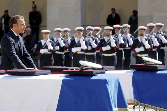 두 군인의 관에 훈장을 수여한 후 예를 갖추고 있는 마크롱 대통령 [AP=연합뉴스]