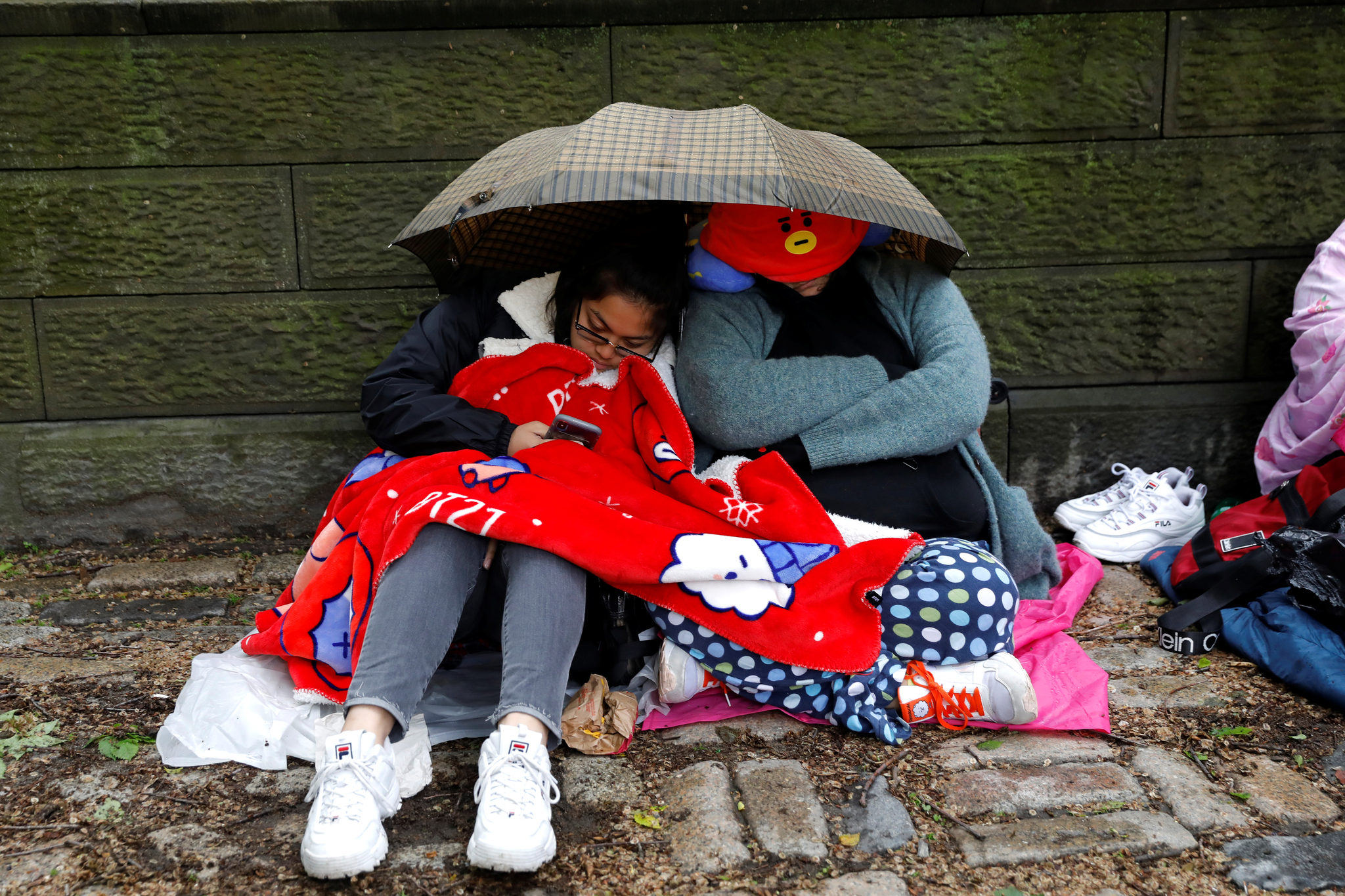 방탄소년단 팬들이 14일(현지시간) 뉴욕 센트럴 파크에서 우산을 쓰고 잠을 청하고 있다. [로이터=연합뉴스]