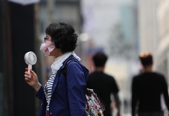 15일 서울 명동거리를 지나는 한 시민이 휴대용 선풍기로 더위를 식히고 있다. [연합뉴스]