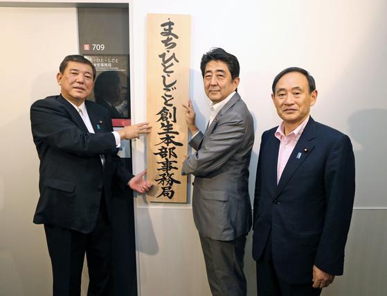 아베 신조 일본 총리(가운데)가 2014년 9월 '마을ㆍ사람ㆍ일 창생본부' 사무국 현판식을 하고 있다. 왼쪽은 이시바 시게루 당시 지방창생상, 오른쪽은 스가 요시히데 관방장관. [지지통신]