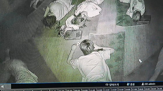 서울의 한 찜질방에서 다른 손님의 휴대전화에서 유심침을 빼내고 있는 A씨(19) [강북경찰서 제공]
