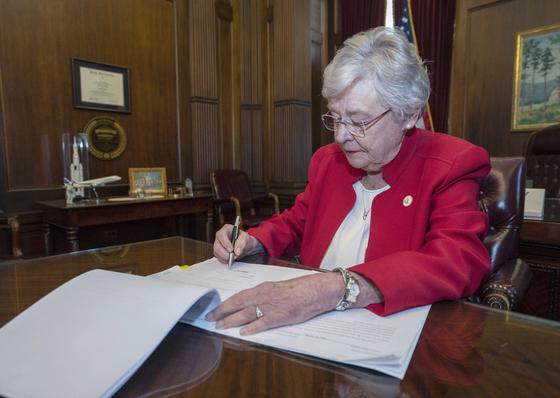 케이 아이비 미 앨라바마 주지사가 15일(현지시간) 여성의 건강에 심각한 위협이 되는 경우를 제외한 모든 낙태를 금지하는 법안에 서명하는 모습. [AP=연합뉴스]