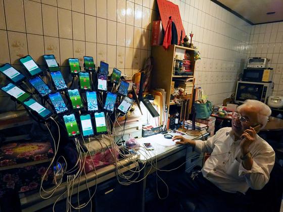 첸 산 위안이 지난 3월 대만 신타이베이 시에서 포케몬 사냥에 사용되는 22개의 핸드폰을 보여주며 통화하고 있다. [EPA=연합뉴스]