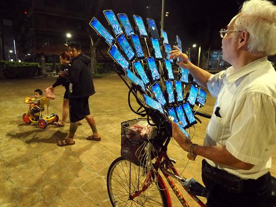 첸 산 위안이 지난 14일 대만 신타이베이 시에서 자전거에 장착된 31개의 핸드폰을 조작하고 있다. [EPA=연합뉴스]