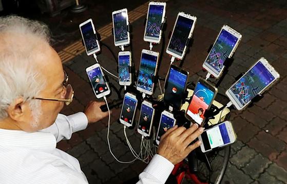 첸 산 위안이 지난해 11월 대만 신타이베이 시에서 자전거에 장착된 15개의 핸드폰을 보여주고 있다.[로이터=연합뉴스]