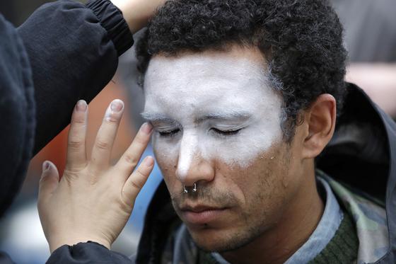지난 해 10월 31일 미국 아마존 본사 앞에서 시위대 중 한 명이 아마존의 안면인식 프로그램 '레코그니션'에 반대하는 의미로 얼굴을 하얗게 칠하고 있다. [AP=연합뉴스]