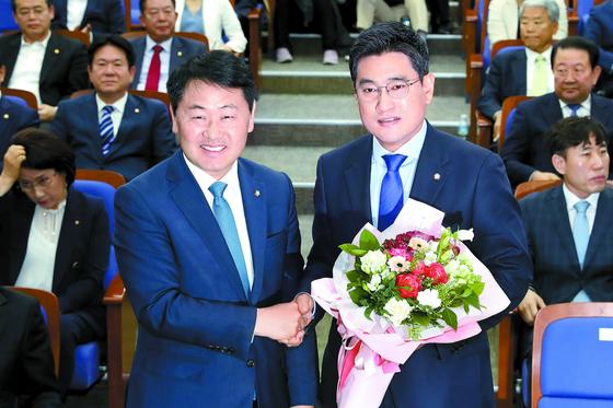 오신환 의원(오른쪽)이 15일 서울 여의도 국회에서 열린 바른미래당 의총에서 김성식 의원을 누르고 신임 원내대표로 선출됐다. 오 원내대표와 김관영 전 원내대표가 악수하고 있다. [뉴스1]
