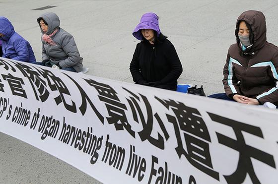 파룬궁 수련자들이 뉴욕의 중국 영사관 앞에서 중국 당국의 탄압에 항의하는 현수막을 앞에 두고 명상을 하고 있다. [AP 연합뉴스]