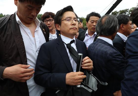 황교안 자유한국당 대표가 18일 오전 광주 북구 운정동 국립5.18민주묘지에서 열린 제39주년 5.18민주화운동 기념식에 참석하러 광주시민들의 항의 속에 입장하고 있다. [청와대사진기자단]
