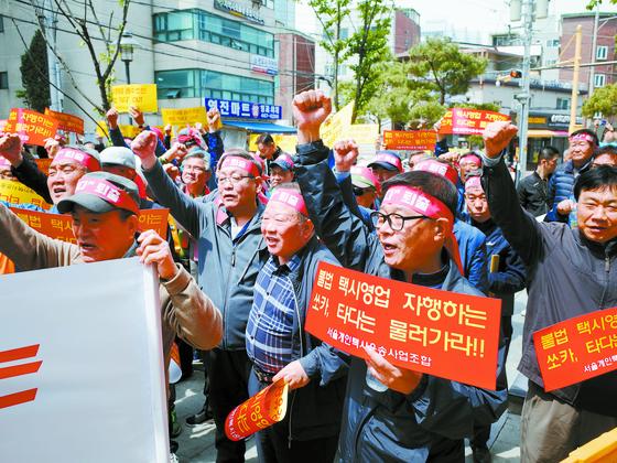 서울시 개인택시운송조합이 지난달 30일 오전 서울 성동구 성수동 카셰어링 서비스 업체 쏘카 서울사무소 앞에서 '타다'(TADA) 서비스 중단을 촉구하는 집회를 열고 있다. [중앙포토]