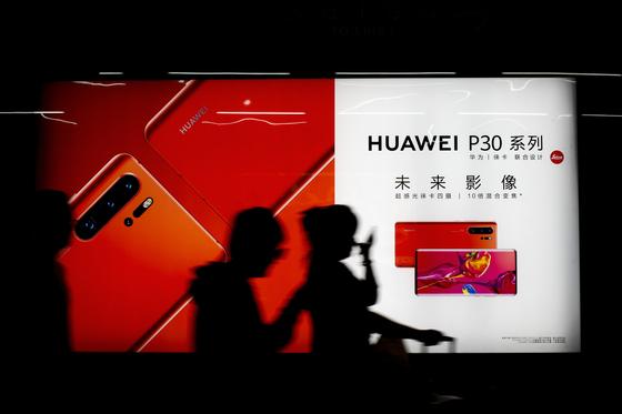 지난 13일 중국 베이징의 한 지하철역 구내에 걸린 화웨이 스마트폰 P30 광고판 앞을 사람들이 지나가고 있다. [AP=연합뉴스]