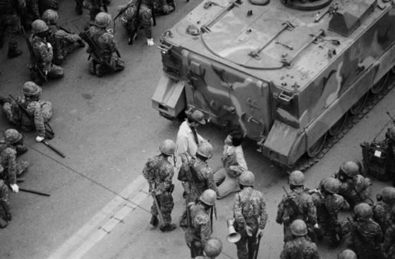 1980년 광주 금남로에서 시민과 학생들이 군사정권 퇴진을 요구하며 대형 버스를 앞세우고 시위하는 학생을 계엄군이 연행해 탱크 앞에서 무릎을 꿇리고 있다. [연합뉴스]