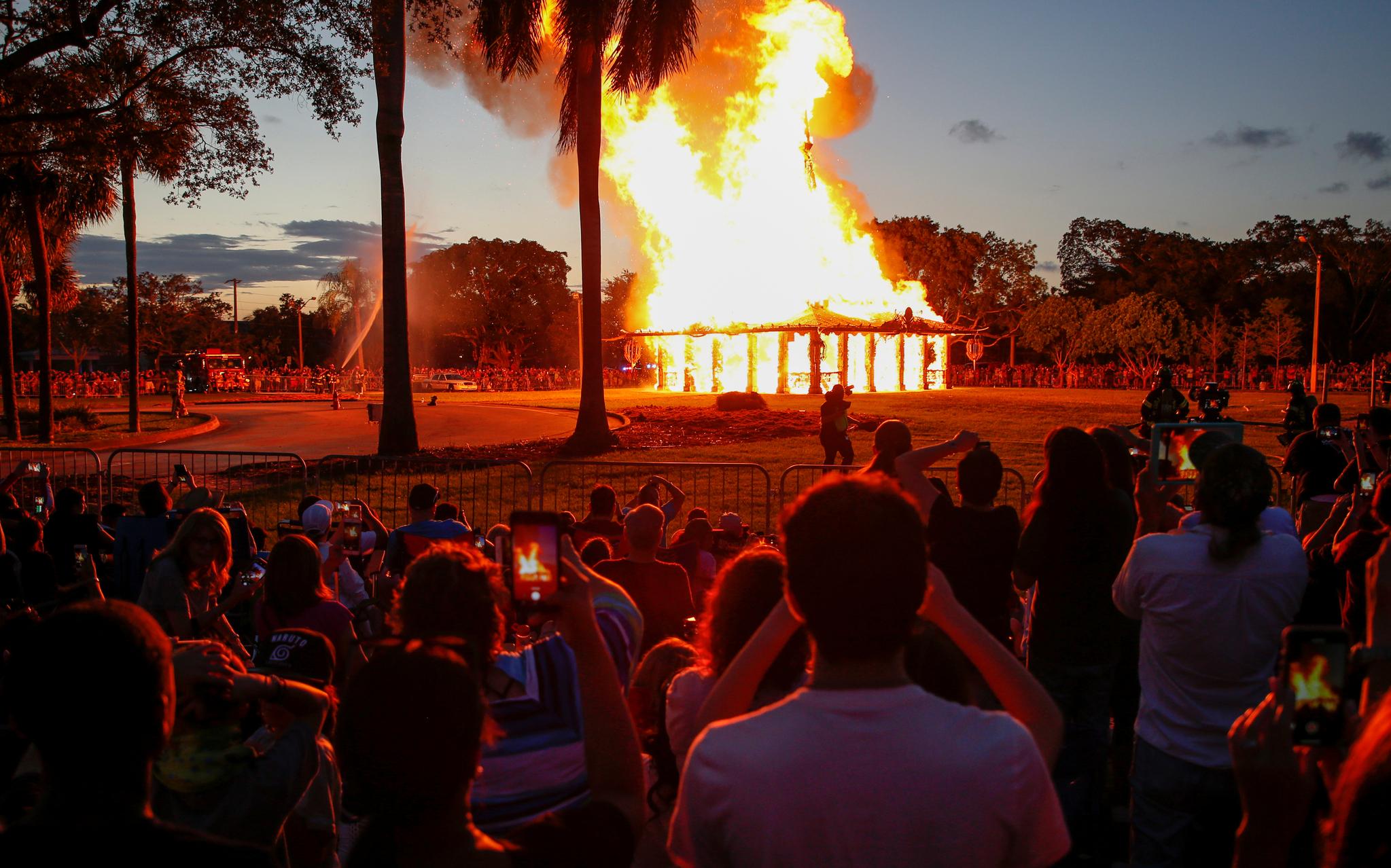 19일(현지시간) 수백명의 시민들이 불타는 사원을 지켜보며 희생자를 추모하고 있다. [로이터-연합뉴스]