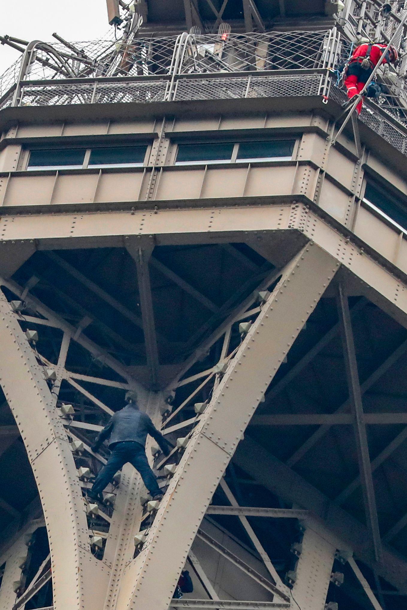 한 남성이20일(현지시간) 맨손으로 에펠탑 3층 밑에서 출동한 구조대와 대화하고 있다.  [AFP=연합뉴스]