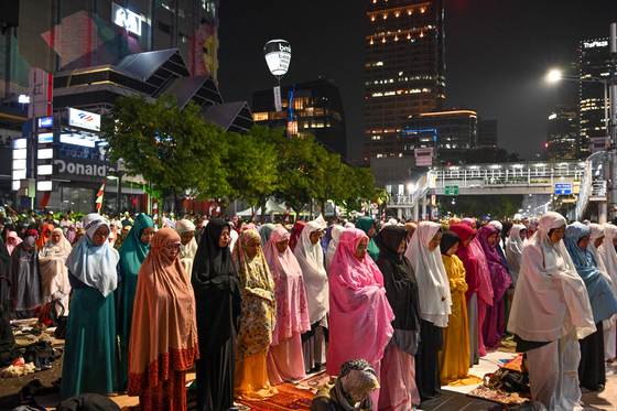 대선 결과 불복 시위에 참가한 무슬림이 21일(현지시간) 인도네시아 자카르타 선거감독위원회 앞에서 밤 기도를 하고 있다.[AFP=연합뉴스]