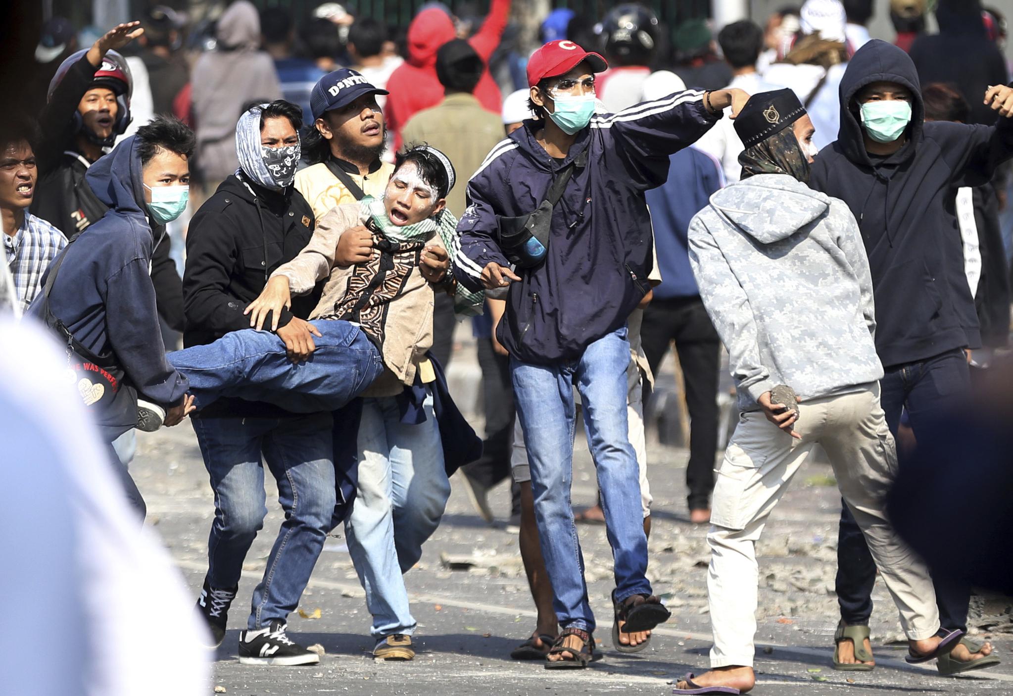 대선 결과 불복 시위에 참가한 야권 지지자들이 22일(현지시간) 인도네시아 자카르타에서 시위를 벌이던 도중 부상자를 옮기고 있다.[AP=연합뉴스]
