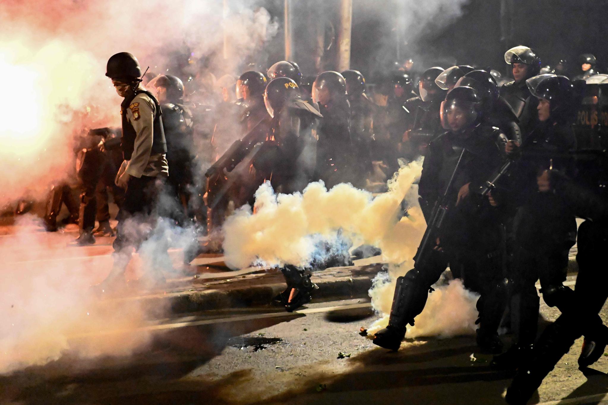 인도네시아 경찰이 22일(현지시간) 자카르타 선거감독위원회 인근에서 시위대를 향해 체류탄을 쏘고 있다. [AFP=연합뉴스]