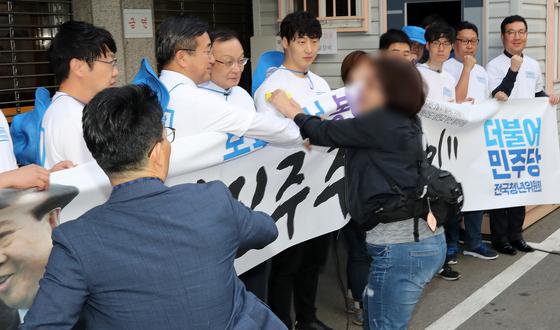 이해찬 더불어민주당 대표가 21일 서울 여의도 당사 앞에서 열린 목포에서 봉하까지 '민주주의의 길' 출정식에서 한 장애인 대표자가 '우리도 함께 가자'며 뛰어들고 있다. 장애인 단체 회원들은 '가짜 등급제 폐지'를 주장하며 당사 진입을 시도 했다. [뉴스1]