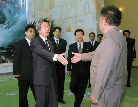 2002년 9월 방북한 고이즈미 준이치로 당시 일본 총리가 김정일 국방위원장과 인사하고 있다. 아베 신조 총리(왼쪽 세 번째)는 관방장관 자격으로 참석했다.