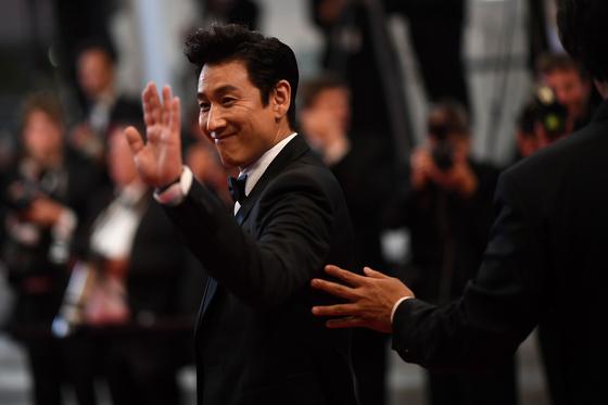 21일 배우 이선균이 여유있는 표정으로 손을 흔들며 상영장을 향하고 있다.[AFP=연합뉴스]