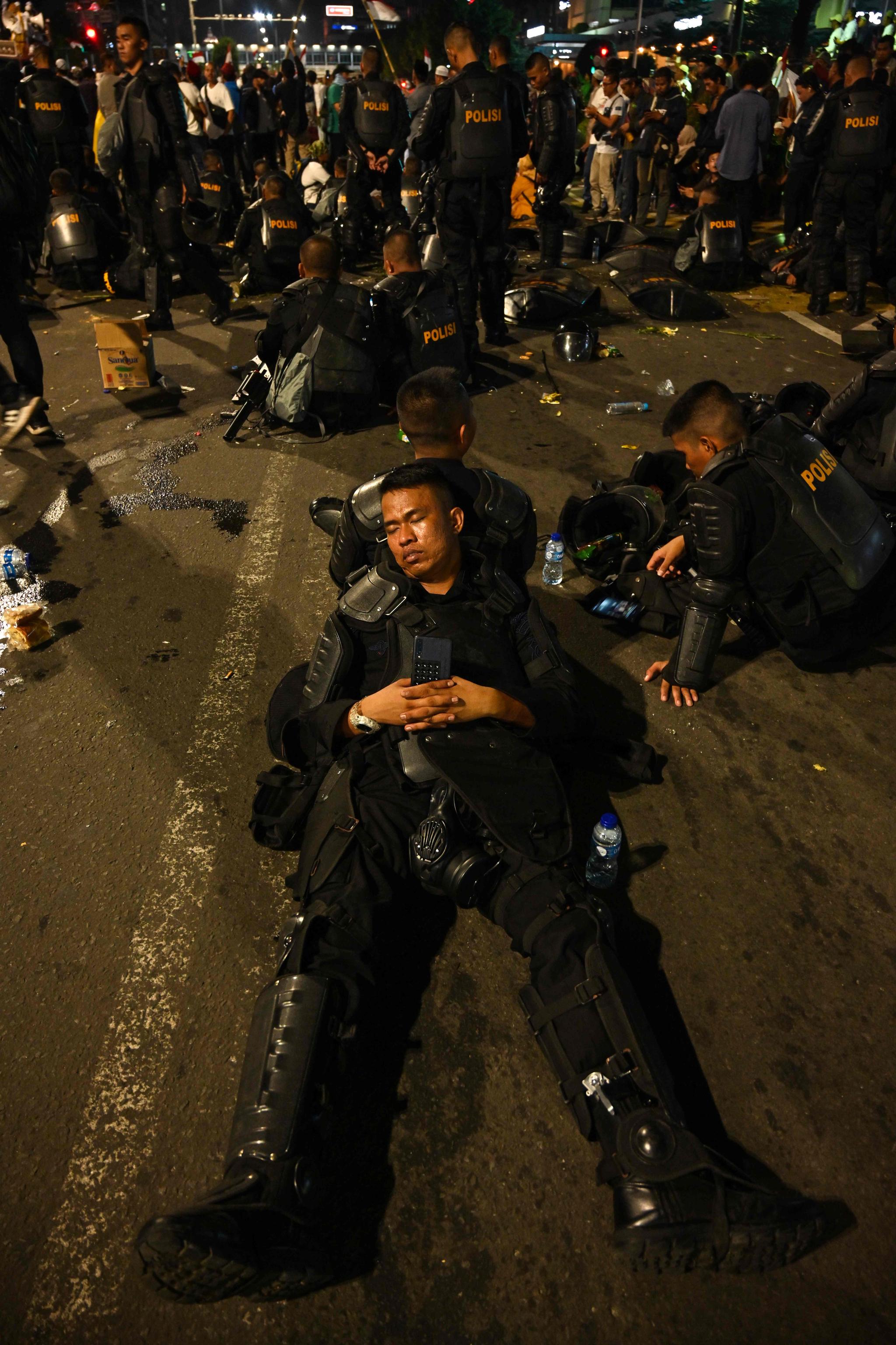 인도네시아 경찰이 21일 자카르타 선거감독위원회 앞에서 시위대가 기도를 하는 동안 휴식을 취하고 있다. [AFP=연합뉴스]