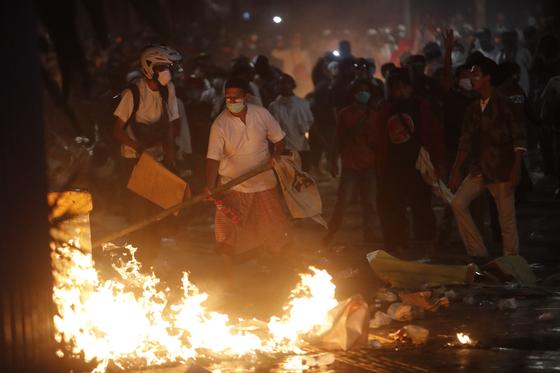 22일 인도네시아 대선 결과에 불복하는 야당 지지자들이 자카르타 시내에서 불을 지르며 경찰과 대치하고 있다. [EPA=연합뉴스]