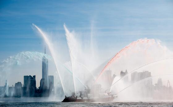 22일(현지시간) 미국 뉴욕에서 소방국(FDNY)의 소방선이 색색의 물줄기를 뿜어내고 있다. [AFP=연합뉴스]