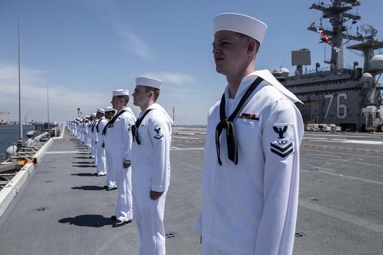 지난 22일 일본 요코스카항을 출항 중인 로널드 레이건함의 갑판에서 미국 해군 수병들이 줄지어 서 있다. [사진 미 해군]