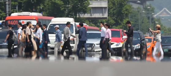 23일 서울 세종대로에서 시민들이 지열이 피어오르는 횡단보도 위를 지나고 있다. [연합뉴스]