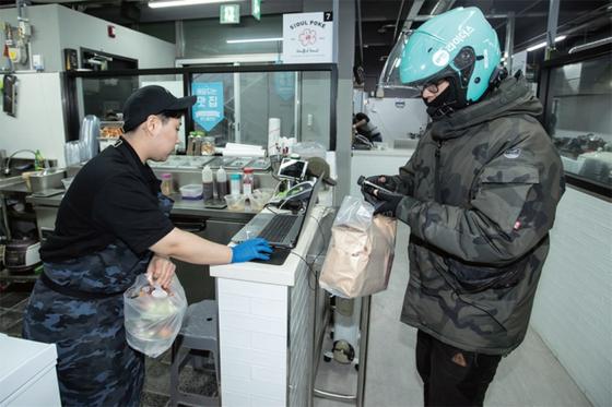 한 식당 직원이 배달원에게 고객이 주문한 음식을 전달하고 있다. 요즘은 레스토랑이나 아이스크림 전문점 등 다양한 업종이 음식 배달 시장에 뛰어들고 있다. [중앙포토]