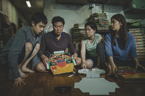 영화 '기생충'에서 전원이 백수인 기택(송강호)네 가족이 좁은 반지하집에서 피자 상자 빨리 접는 방법을 연구하고 있다. [사진 CJ엔터테인먼트]