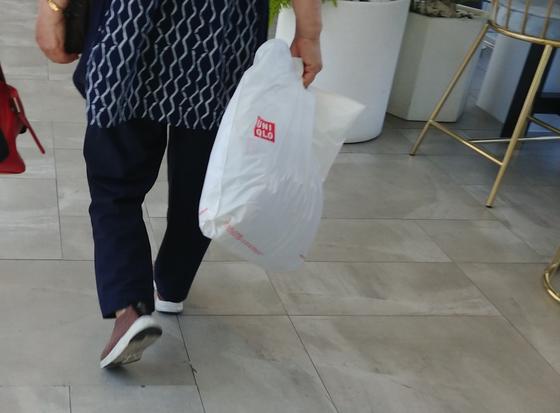 22일 한 시민이 서울 중구 대형백화점 내 의류매장에서 산 옷을 담은 생분해 비닐봉투를 들고 있다. 김정연 기자
