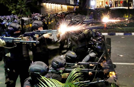 인도네시아 경찰이 22일(현지시간) 새벽 시위대를 향해 발포하고 있다. [로이터=연합뉴스]