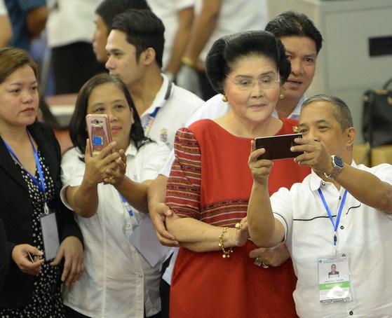 22일 딸의 당선식에 참석한 이멜다가 선관위 관계자들과 기념사진을 찍고 있다.[AFP=연합뉴스]