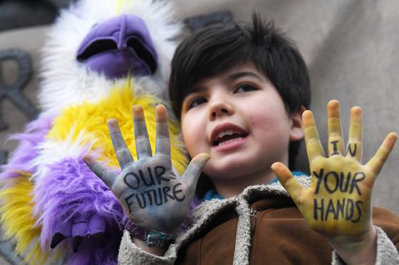 지난 3월 영국 런던에서 열린 '미래를 위한 금요일(#FridayForFuture)' 시위에 참여한 소년 손바닥에 '우리의 미래는 당신들 손에 있다'고 적혀있다. [EPA=연합뉴스]