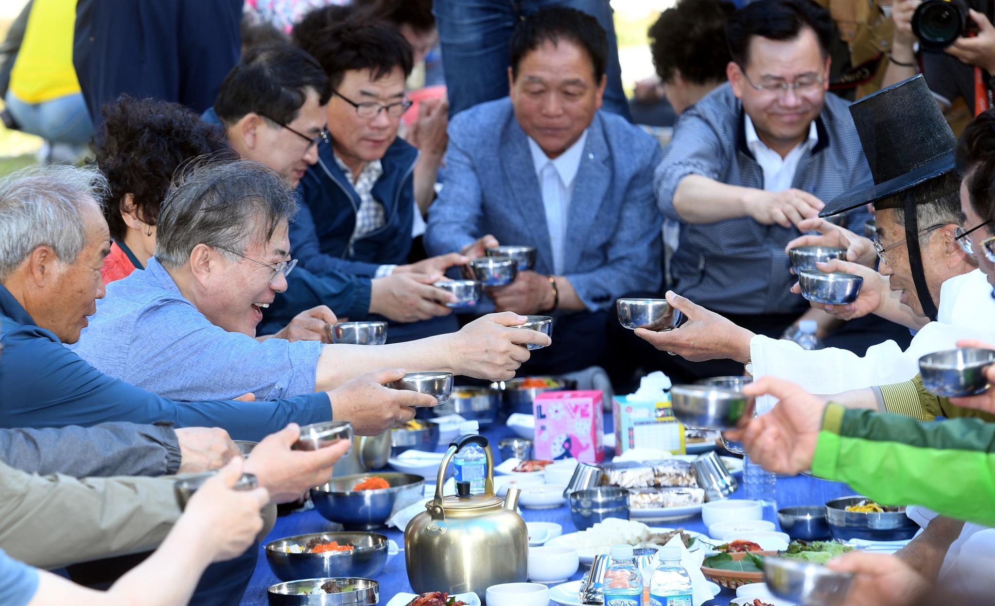 문재인 대통령(왼쪽 두 번째)이 24일 오전 경북 경주시 옥산마을을 방문, 모내기를 한 뒤 주민들과 함께 새참을 먹고 있다. [청와대사진기자단]