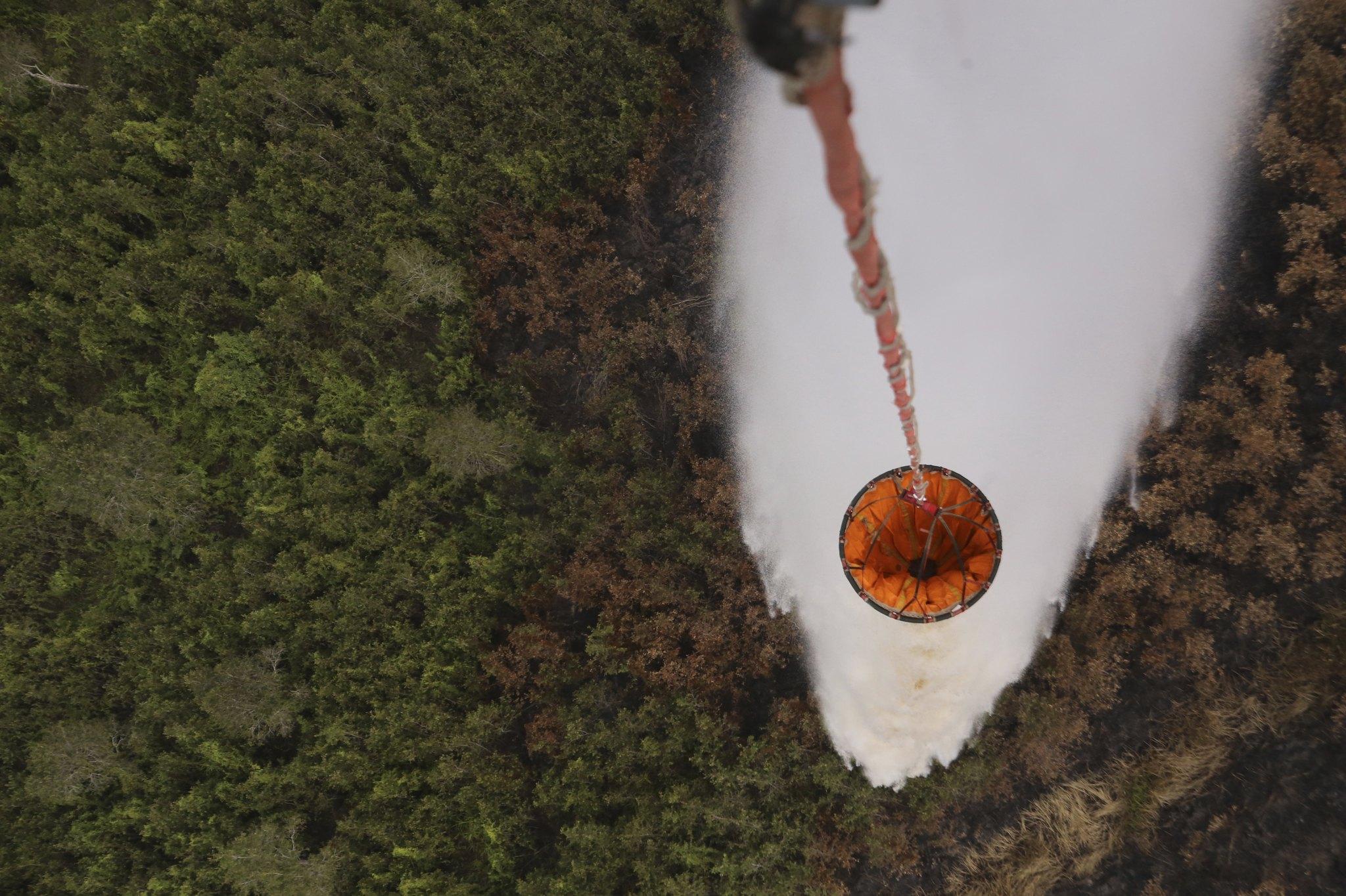 지난해 7월 인도네시아 남수마트라의 팔리 지역에서 산불로 인한 짙은 연무가 발생하자 산불을 진화하기 위해 헬리콥터에서 물을 뿌리고 있다. [AP=연합]