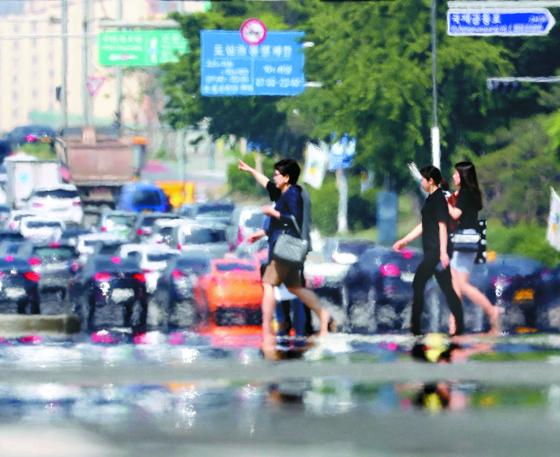 서울에 올해 첫 폭염특보가 발효된 24일 오후 시민들이 서울 여의도 공원 옆 건널목을 건너고 있다. 기상청은 휴일인 26일에도 동해안과 중부 내륙, 경북 내륙 등지를 중심으로 땡볕 더위가 이어질 것으로 예보했다. 신인섭 기자