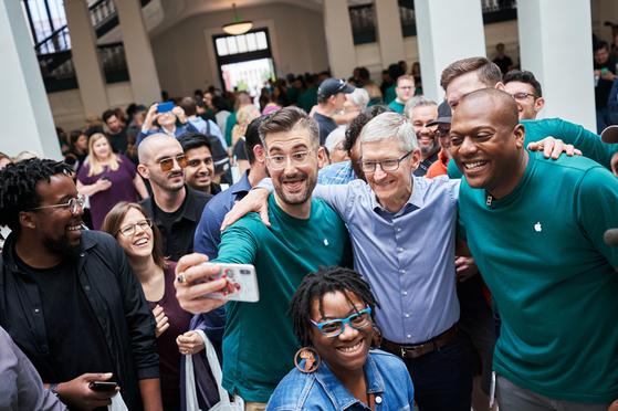 애플이 워싱턴 DC 카네기도서관에 플래그십 매장을 연 지난 11일(현지시간) 팀 쿡 최고경영자가 녹색 셔츠를 입은 애플스토어 직원들과 기념 촬영을 하고 있다. [사진 애플 홈페이지]