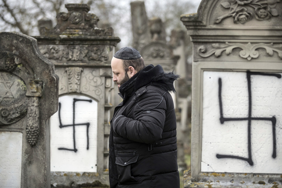 지난해 12월 프랑스 동부 스트라스부르 근처의 헤를리스하임 유대인 묘지에서 한 시민이 훼손된 묘지 사이를 걷고 있다. 이 묘지의 37개의 무덤과 유대인 대학살 희생자들을 위한 기념비에 독일 나치의 표시가 그려져 있다. [AP=연합뉴스]