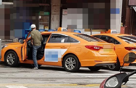 티셔츠와 청바지, 모자를 착용한 한 법인택시 기사가 지난해 4월 서울 강북구 기사식당 앞에서 택시에 오르고 있다. 임선영 기자