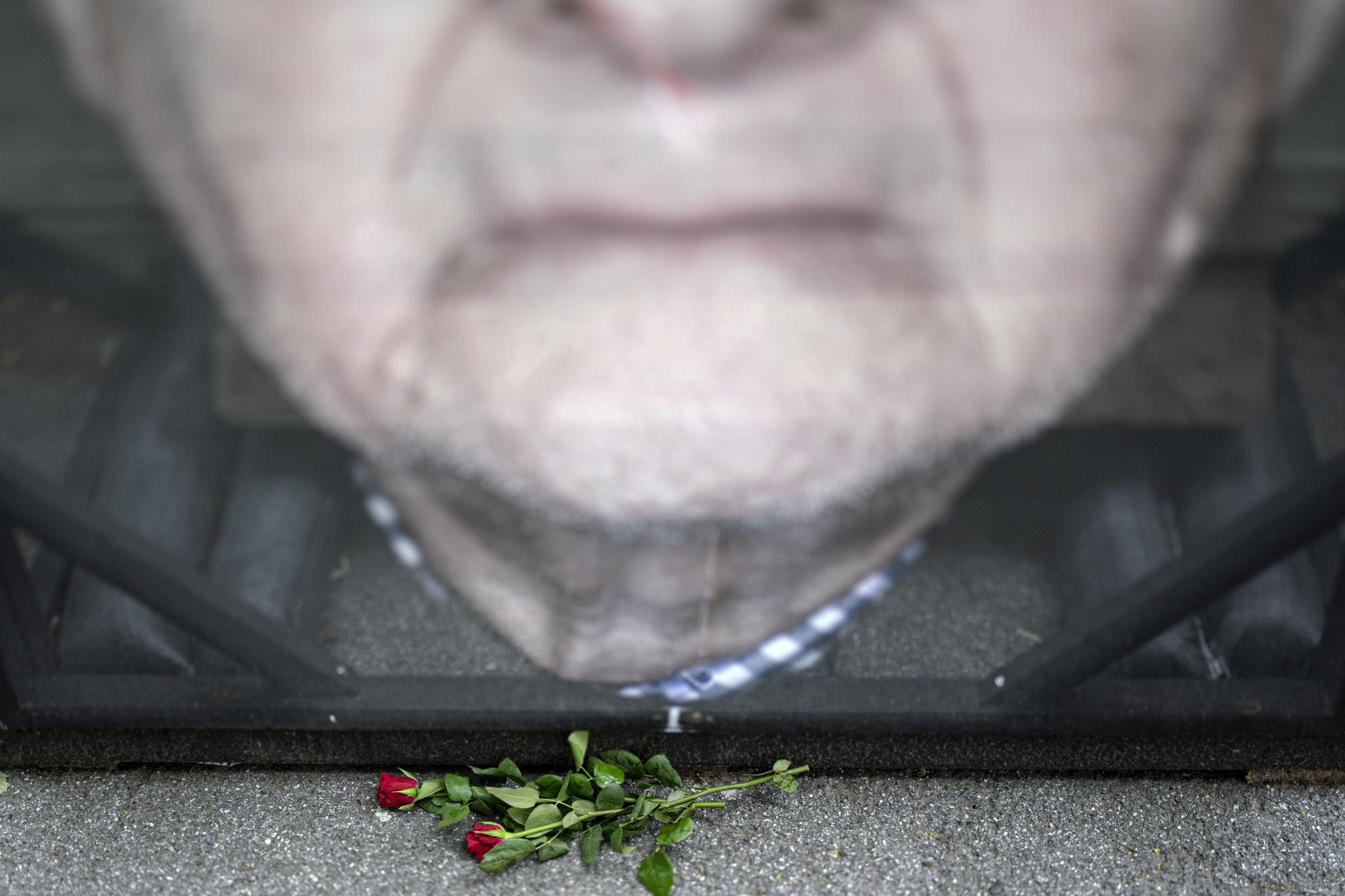 27일(현지시간) 훼손된 초상화 앞에 홀로코스트 생존자의 마음을 위로하듯이 누군가가 두고간 장미꽃이 놓여있다. [EPA=연합뉴스]