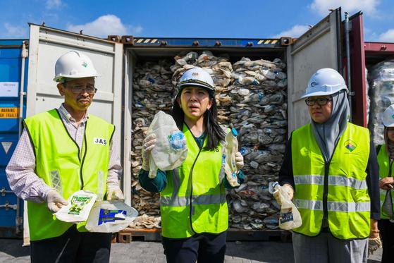 말레이시아 여비인 에너지·과학기술·환경·기후변화부 장관(가운데)이 28일(현지시간) 쿠알라룸푸르 외곽 클랑 항에서 호주에서 들어온 프라스틱 쓰레기를 들어보이고 있다. [AFP=연합뉴스]